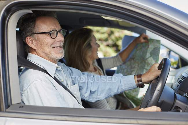 Senior couple traveling by car and woman reading map. — Stock Photo
