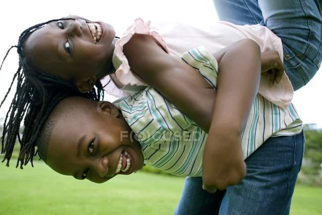 Niño levantando hermana en la espalda en el jardín . - foto de stock
