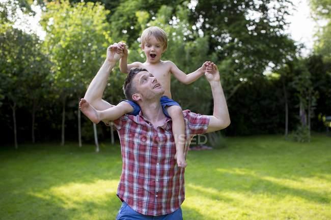 Père portant son fils sur les épaules dans le jardin . — Photo de stock