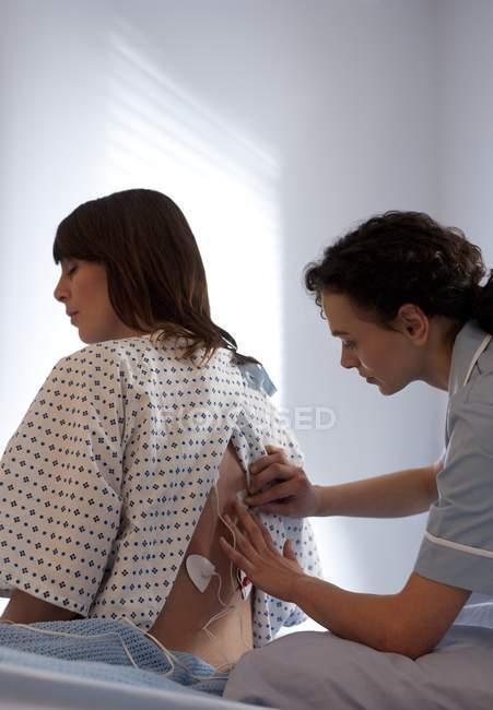 Медсестра применяет к спине пациента стимуляцию транскатанного электрического нерва . — стоковое фото