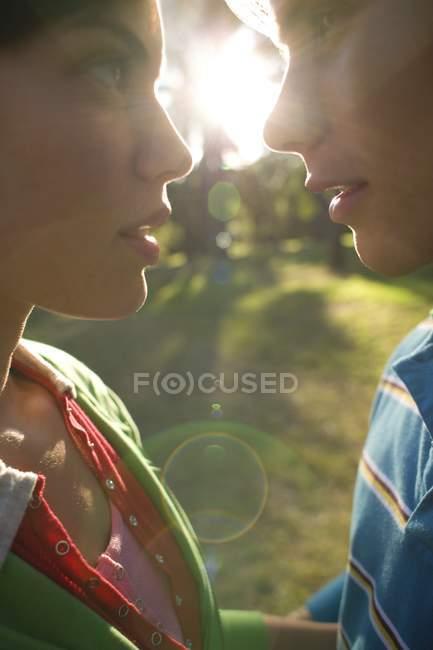 Joven pareja de enamorados que se inclina para besar en la luz del sol suave. - foto de stock