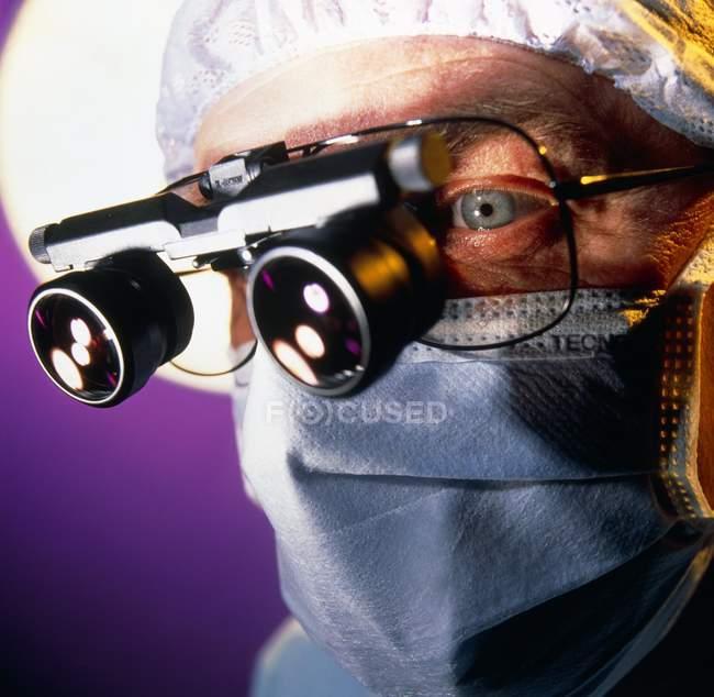 Chirurgo con lenti di ingrandimento microchirurgiche sopra gli occhiali . — Foto stock