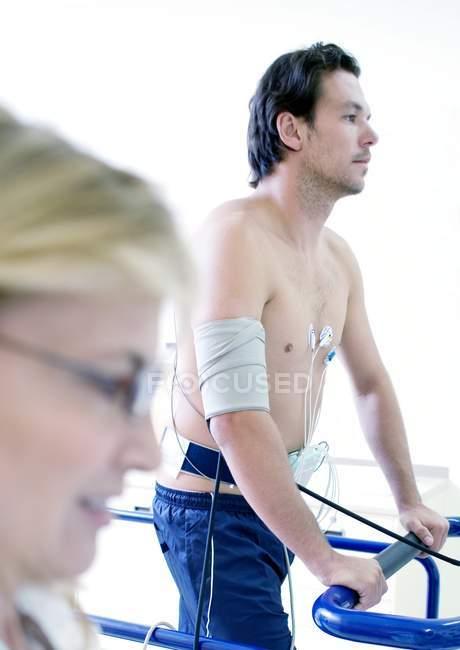 Médico maduro probando corazón de atleta masculino en cinta de correr . - foto de stock