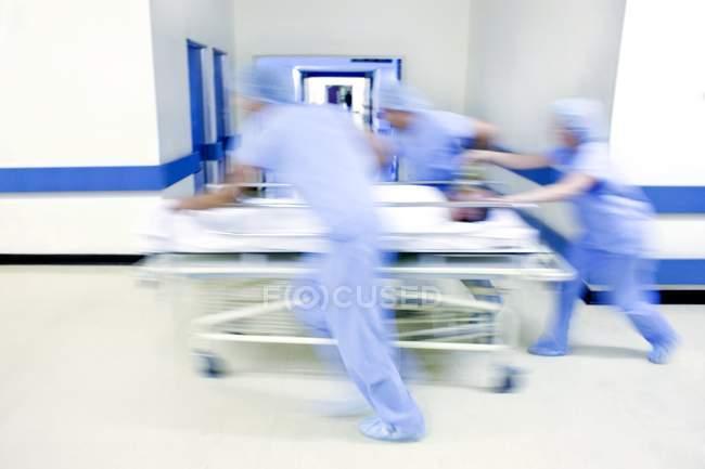 Надзвичайних команда, штовхаючи лікарні Герні з пацієнтом в коридорі. — стокове фото