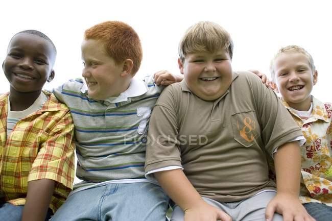Портрет группы мальчиков младшего возраста, сидящих бок о бок на открытом воздухе . — стоковое фото