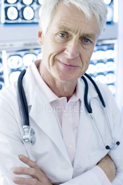 Senior radiologist with arms crossed standing in front CT scans in hospital. — Stock Photo