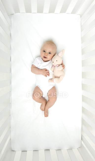 Baby boy lying down in cot with toy. — Stock Photo