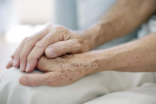 Close-up of senior couple holding hands. — Stock Photo
