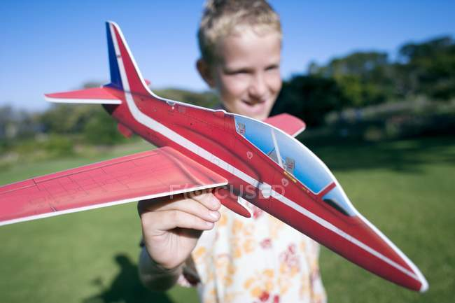 Boy playing with model aircraft in park. — Stock Photo