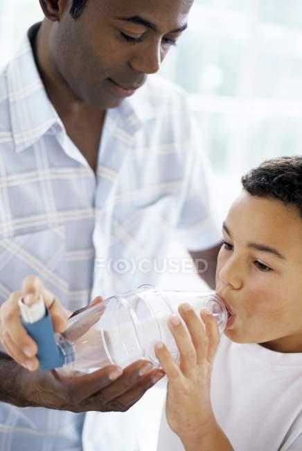 Батько, допомагаючи астматичний сина, використовуючи spacer інгалятор з пластикових палати. — стокове фото