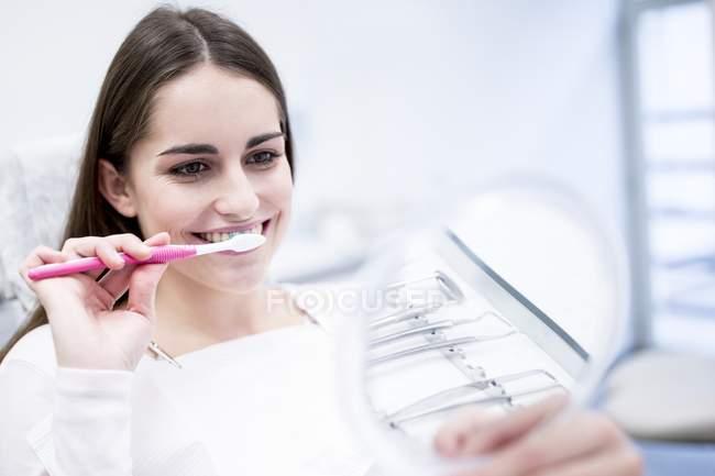 Paziente donna lavarsi i denti mentre si guarda allo specchio . — Foto stock