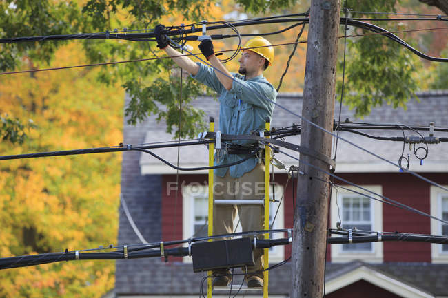 Lineman working on cables at power pole. — Stock Photo