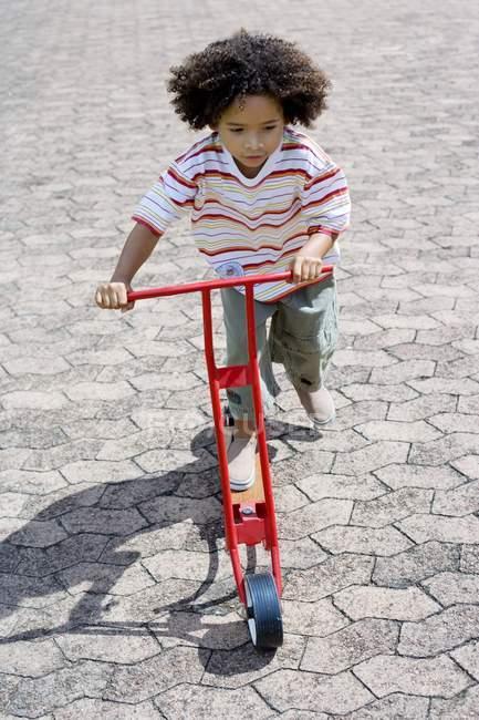 Pequeño niño montar a caballo empuje la vespa - foto de stock