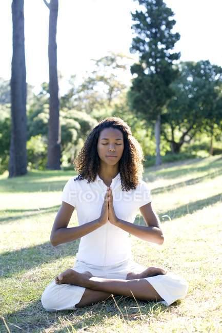 Jeune femme méditant ensemble avec les mains. — Photo de stock