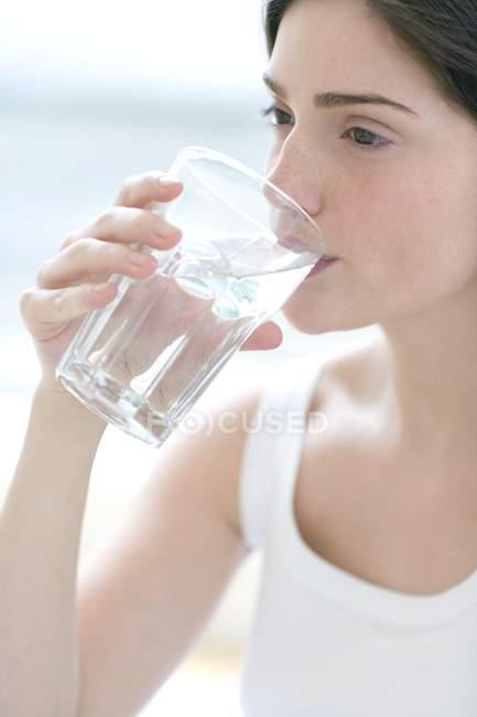 Giovane donna che beve vetro di acqua pulita . — Foto stock
