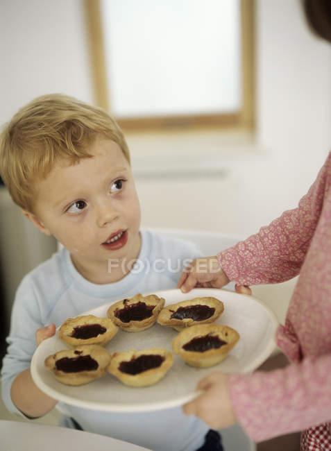 Irmã irmão oferecendo recém-assados tortas de geleia na placa. — Fotografia de Stock