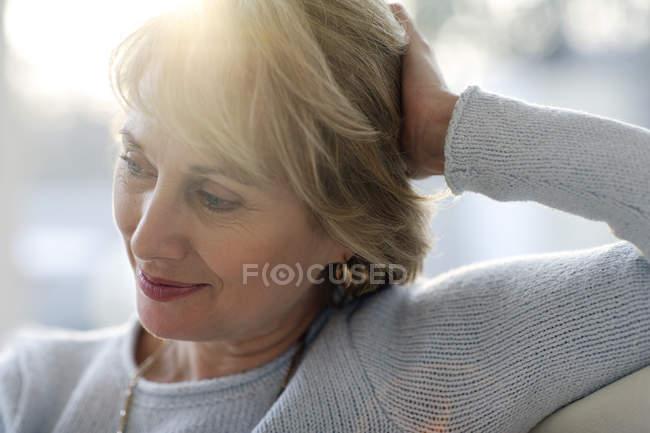Mujer madura sonriendo y mirando hacia otro lado - foto de stock