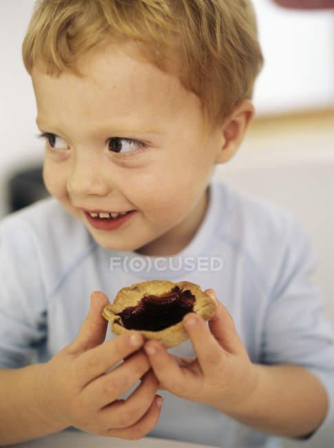 Chico alegre sosteniendo mermelada tarta . - foto de stock