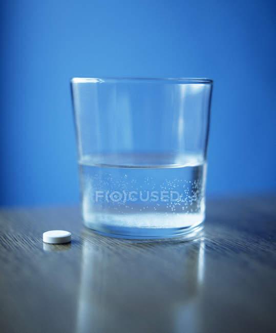 Таблетки поруч зі склянкою води на стіл. — стокове фото