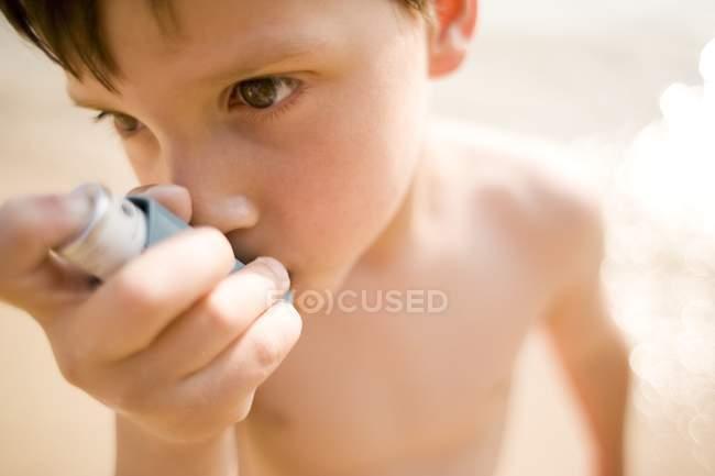 Menino asmático usando inalador na praia . — Fotografia de Stock