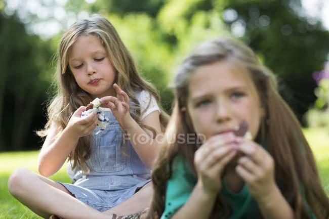 Meninas comendo sorvete no jardim . — Fotografia de Stock