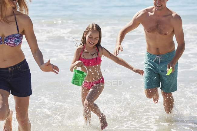 Girl playing on beach with parents. — Stock Photo