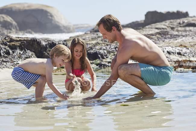 Отец, играть с сыном и дочерью на пляже — стоковое фото