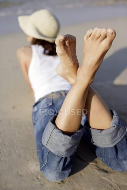 Женщина в джинсы и кепку, лежа на фронте на пляже, вид сзади. — стоковое фото