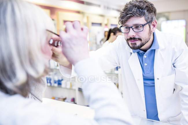 Optometrist trying glasses on woman in shop. — Stock Photo