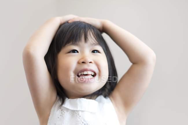 Menina asiática com as mãos na cabeça sorrindo, tiro estúdio . — Fotografia de Stock