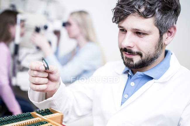 Optometrist holding lens in hand in clinic. — Stock Photo