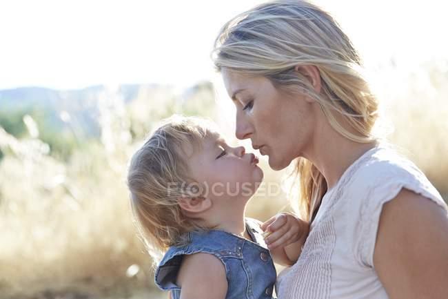 Madre a hija de niño besos al aire libre. - foto de stock