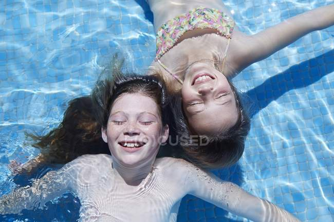 Two girls floating in swimming pool with eyes closed, high angle view. — Stock Photo