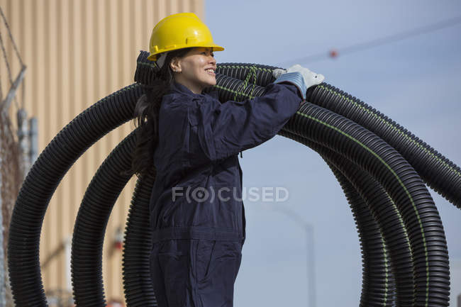 Power engineer moving flexible drainpipes — Stock Photo