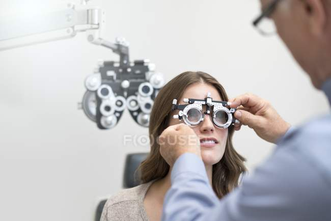 Doctor wearing on woman eyesight testing spectacles. — Stock Photo