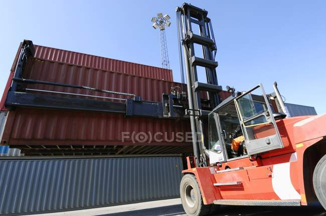 Forklift truck lifting shipping container. — Stock Photo