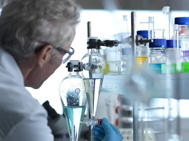 Scienziato osservando chimica esperimento in laboratorio. — Foto stock