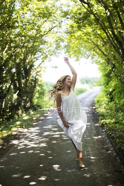 Woman in white dress dancing on country lane. — Stock Photo