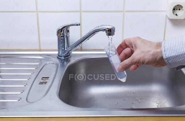 Tubo de teste de enchimento manual de pessoa com água da torneira . — Fotografia de Stock