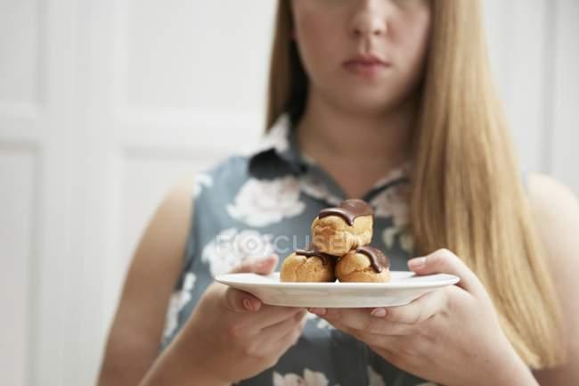 Mujer sosteniendo plato de chocolate eclairs - foto de stock