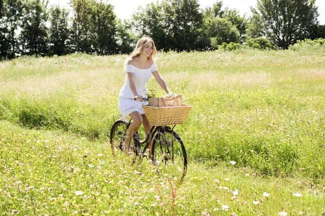 Donna in bicicletta in campo . — Foto stock