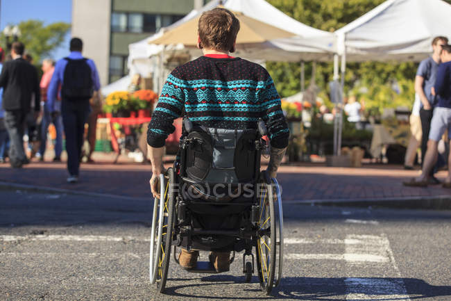 Rear view of young man in wheelchair at city with people in background. — Stock Photo