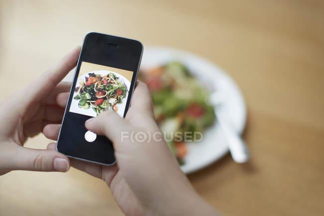 Mains féminines prendre photo de nourriture avec le smartphone — Photo de stock