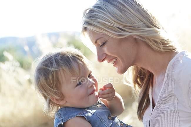 Mère et tenant tout-petit fille et riant à l'extérieur . — Photo de stock