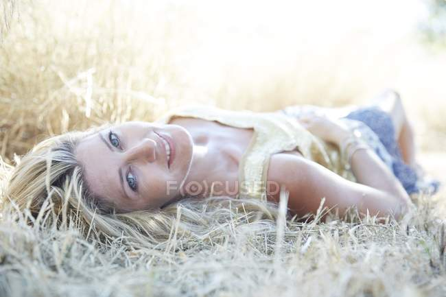 Mid adult woman lying down on grass and smiling. — Stock Photo