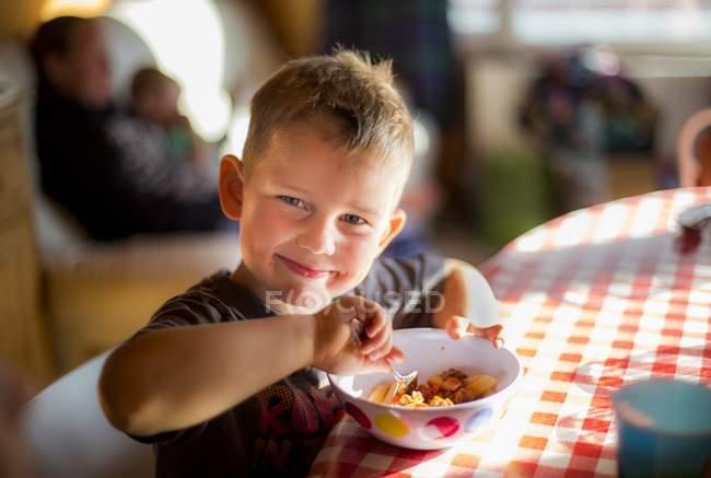 Мальчик сидит за столом и пищи — стоковое фото