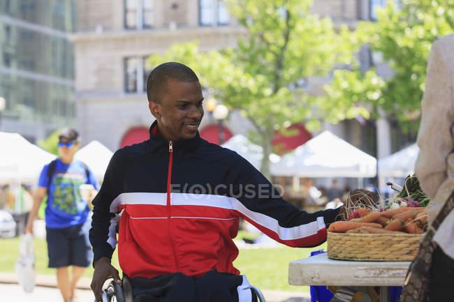 Mann im Rollstuhl shoppt am Gemüsestand in der Stadt. — Stockfoto