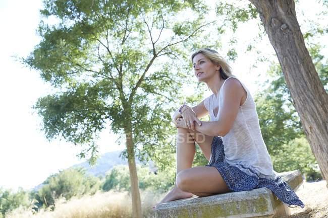Mujer adulta media sentados entre los árboles del parque - foto de stock