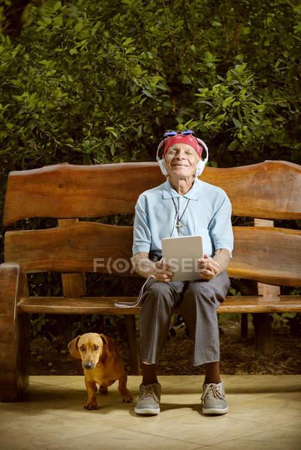 Старший людина сидить на лавці і слухати музику з собакою. — стокове фото