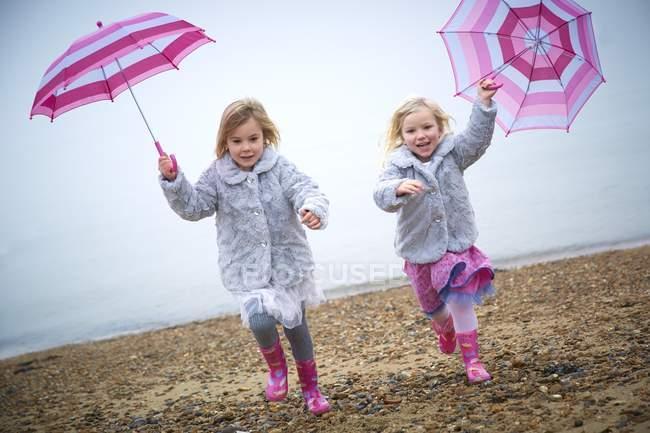Две дошкольника девочки на пляже и проведение розовый зонтики. — стоковое фото